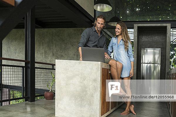 Lächelndes Paar mit Laptop in moderner minimalistischer Küche im zeitgenössischen Designhaus