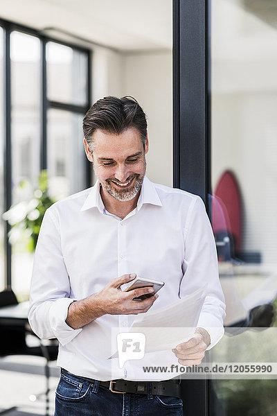 Lächelnder Geschäftsmann beim Blick auf Handy und Dokumente