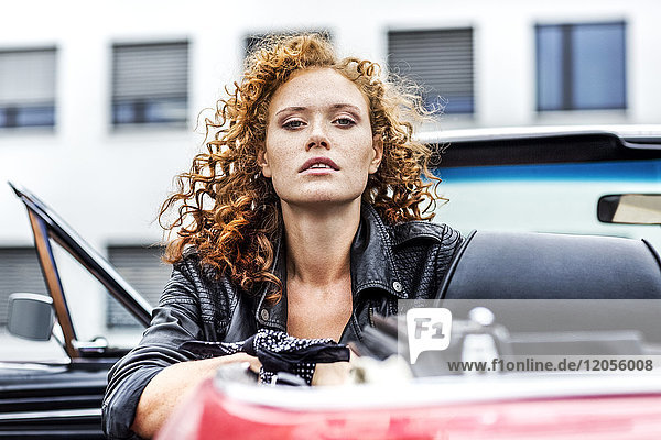 Portrait of confident redheaded woman in sports car