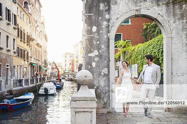 Italien  Venedig  Brautpaar geht Hand in Hand durch den Torbogen