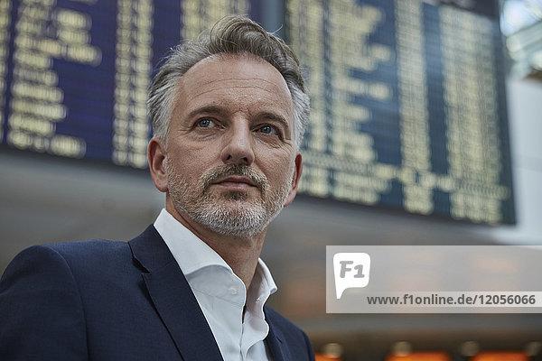 Geschäftsmann am Flughafen vor der An- und Abreisetafel