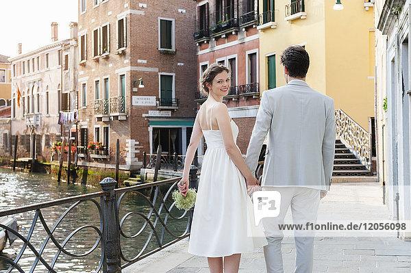 Italien,  Venedig,  glückliches Brautpaar geht Hand in Hand