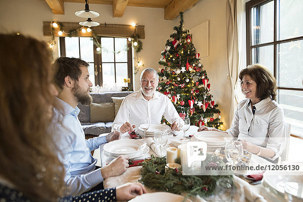 Smiling senior man with family at Christmas dinner table