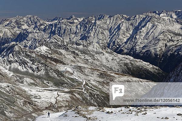 Österreich  Tirol  Ötztal  Sölden  Frau in schneebedeckter Landschaft mit Blick auf die Ötztaler Gletscherstraße