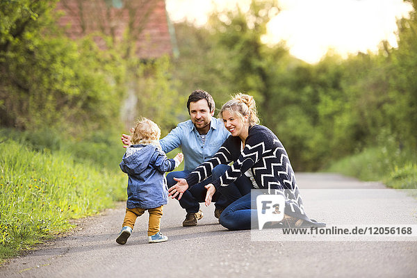 Kleiner Junge mit Eltern auf dem Feldweg