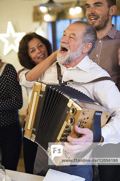 Senior Mann spielt Akkordeon für glückliche Familie an Weihnachten