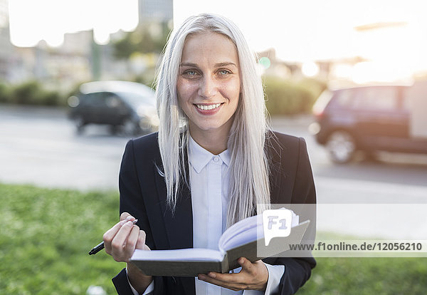 Portait of smiling young businesswoman with notebook in the city