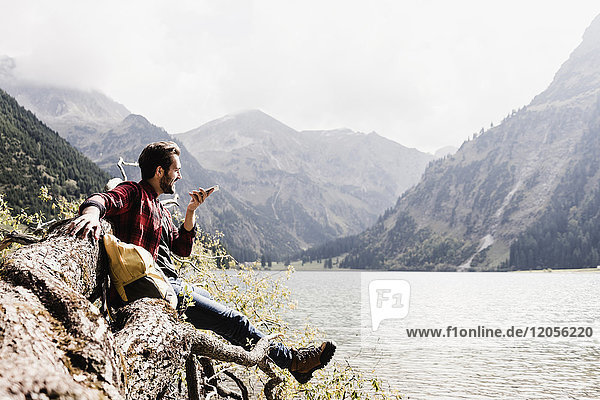 Österreich,  Tirol,  Alpen,  Wanderer auf Baumstamm am Bergsee per Handy