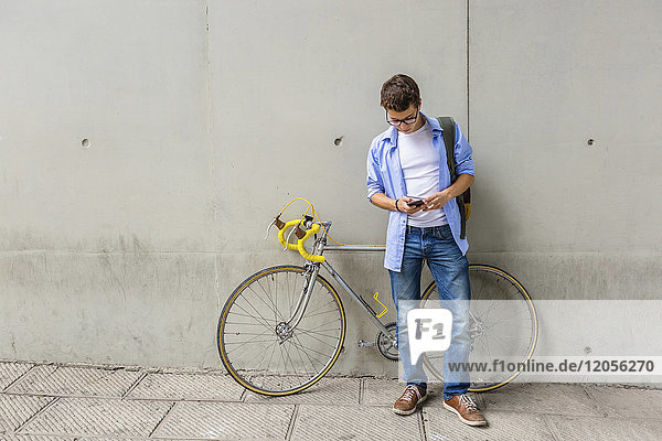 Junger Mann mit Rennrad beim Blick auf das Handy vor der Betonwand