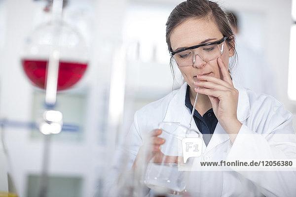 Wissenschaftlerin im Labor mit Becherglas und Pipette