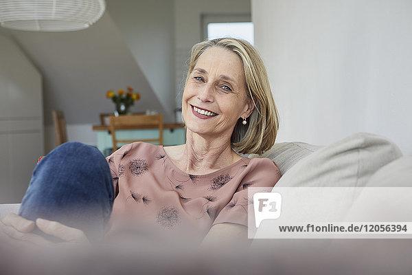 Porträt der lächelnden reifen Frau zu Hause auf dem Sofa