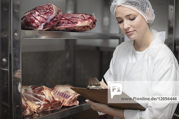Woman with clipboard in storehouse of a butchery