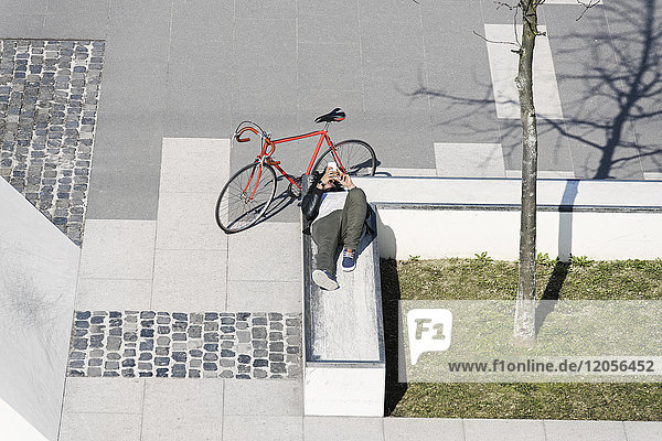 Man relaxing in city skatepark with smartphone next to his bicycle