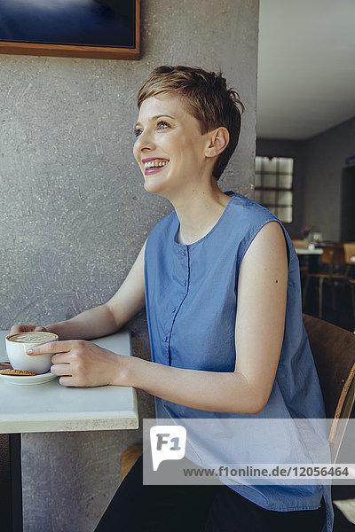 Glückliche Frau mit einer Tasse Kaffee im Café