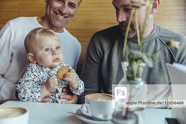 Schwules Paar sieht ihr Baby im Cafe an
