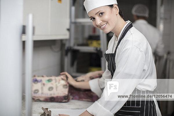 Porträt einer lächelnden Frau in einer Metzgerei