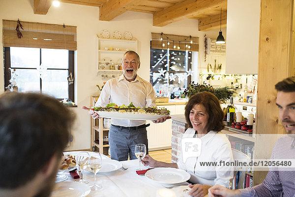 Fröhlicher älterer Mann serviert Fisch für die Familie beim Weihnachtsessen