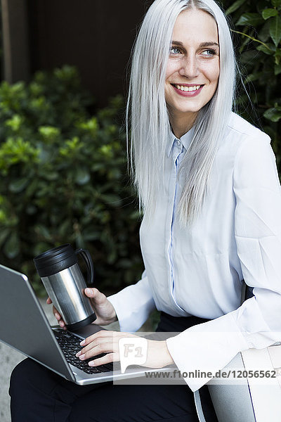 Smiling young businesswoman sitting on a wall with coffee mug and laptop