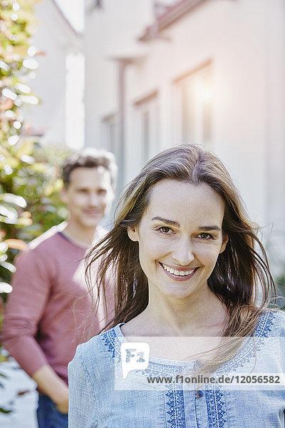 Porträt einer lächelnden Frau mit Mann im Hintergrund