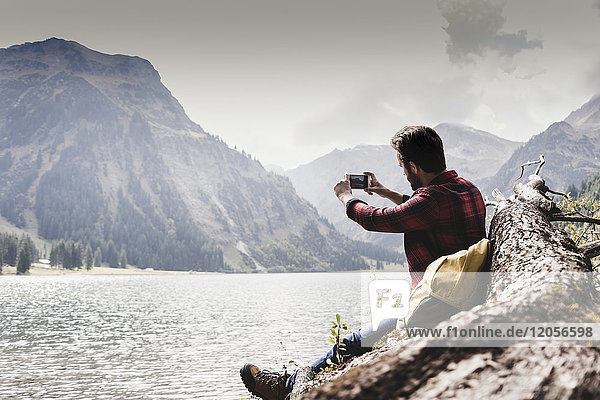 Austria  Tyrol  Alps  hiker sitting on tree trunk at mountain lake taking cell phone picture