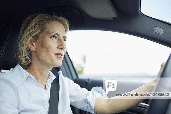 Blonde Geschäftsfrau beim Autofahren