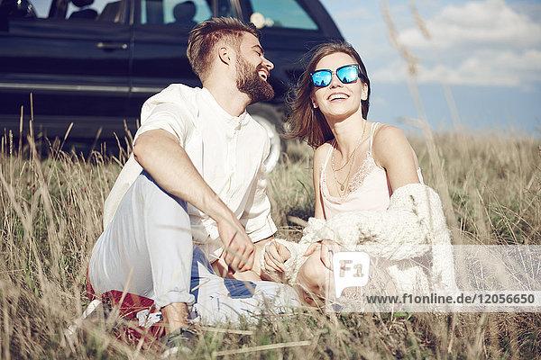 Glückliches junges Paar sitzt auf dem Feld neben dem Auto