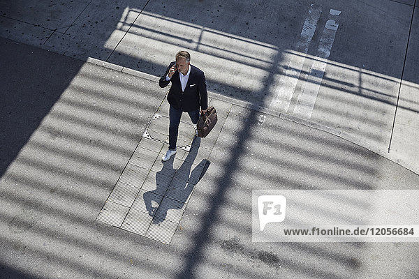 Geschäftsmann am Telefon auf dem Bürgersteig  Draufsicht