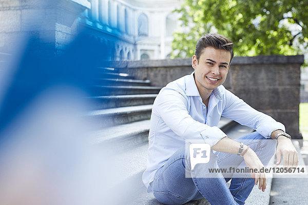 Porträt eines lächelnden jungen Mannes  der auf einer Treppe sitzt.