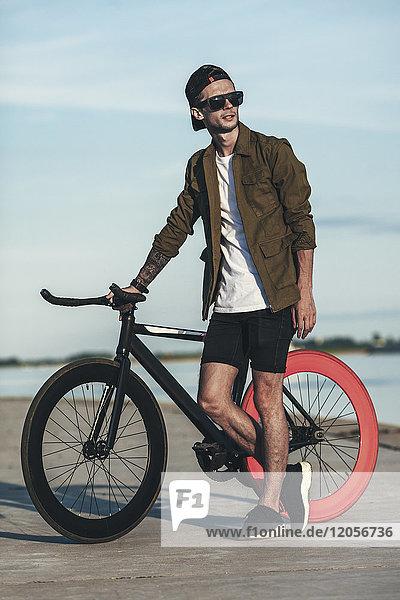 Junger Mann mit Fixie Bike am Wasser