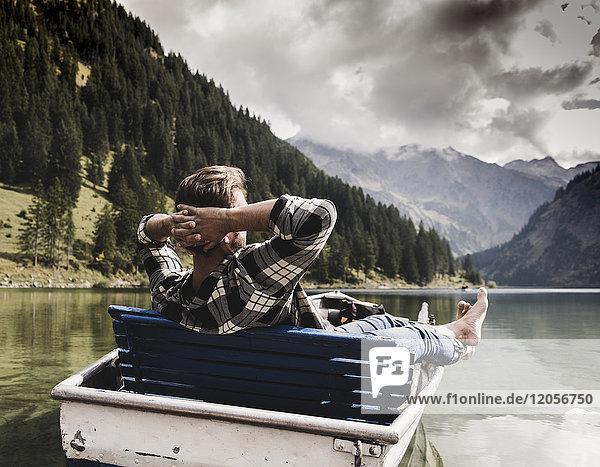 Österreich  Tirol  Alpen  entspannter Mann im Boot auf dem Bergsee