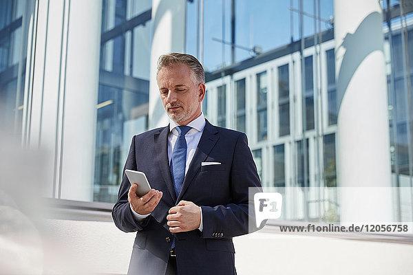 Portrait eines Geschäftsmannes beim Blick aufs Handy