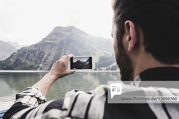 Österreich  Tirol  Alpen  Mann macht Handyfoto von Berglandschaft