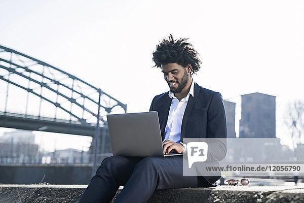 Smiling businessman sitting at the riverside using laptop