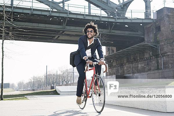 Smiling businessman riding bicycle at riverside bridge