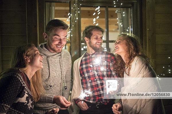 Glückliche Freunde  die nachts im Freien funkeln.