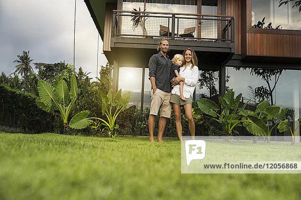 Porträt einer lächelnden Familie  die vor ihrem Designhaus steht  umgeben von einem üppigen tropischen Garten.