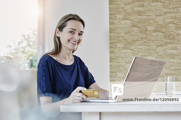 Porträt einer lächelnden Frau beim Online-Shopping