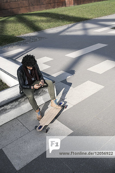 Man sitting in skatepark with longboard typing on smartphone