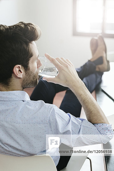 Young businessman working in office  drinking water