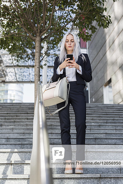Young businesswoman checking cell phone on stairs in the city