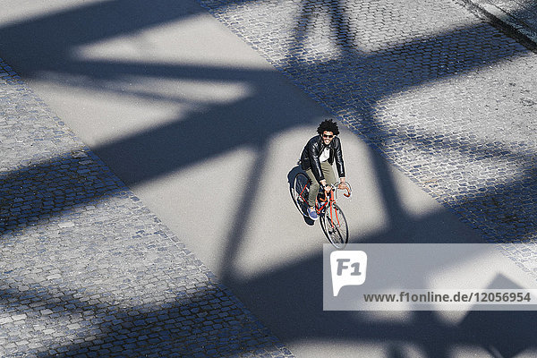 Elevated view of smiling man with sunglasses riding bicycle