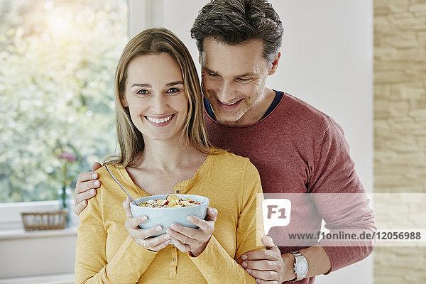 Glückliches Paar hält Schale mit Müsli zu Hause