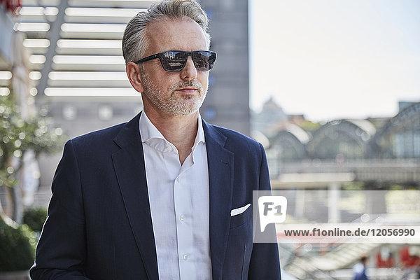 Geschäftsmann mit Sonnenbrille wartet am Flughafen