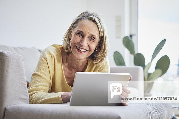 Lächelnde reife Frau zu Hause mit Tablette auf dem Sofa