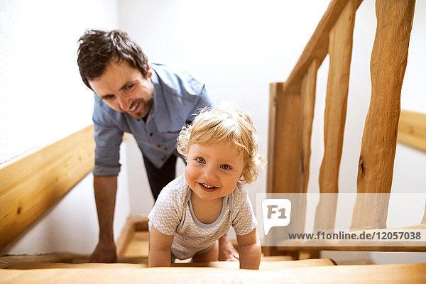 Vater mit kleinem Jungen auf Holztreppe zu Hause