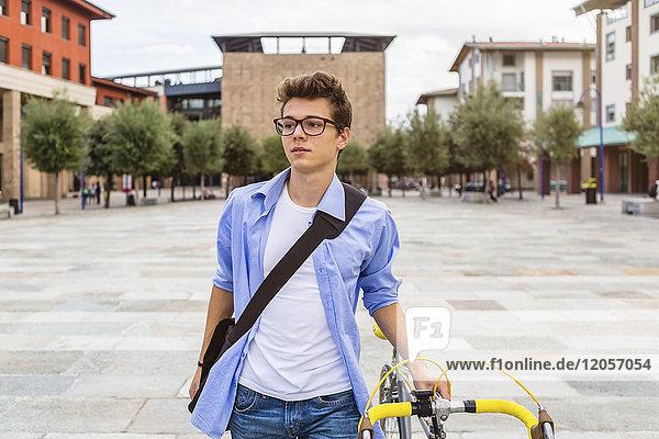 Porträt eines jungen Mannes  der sein Fahrrad schiebt