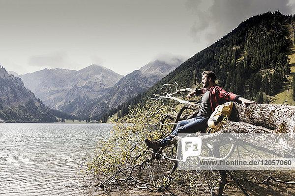 Österreich  Tirol  Alpen  Wanderer entspannen auf Baumstamm am Bergsee