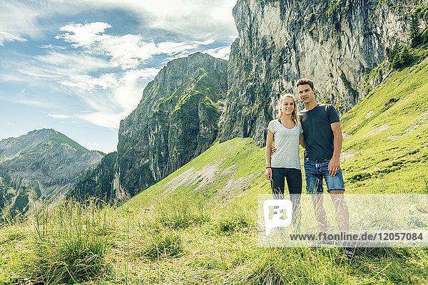 Deutschland  Bayern  Pfronten  Portrait eines jungen Paares auf der Alm bei Aggenstein