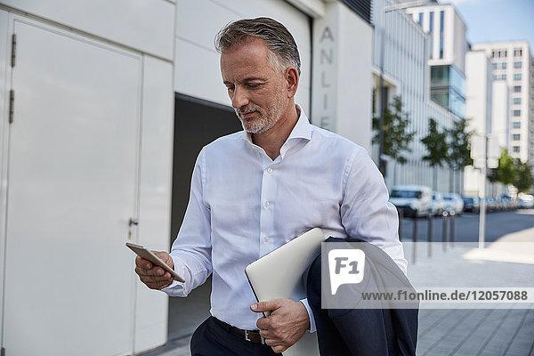 Geschäftsmann beim Blick aufs Handy