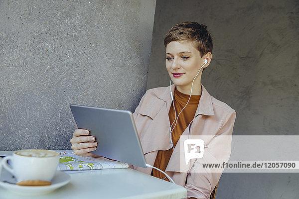 Frau mit Tablette und Ohrstöpseln im Cafe